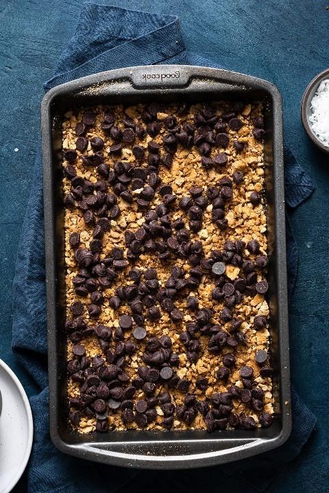 Mostrando cómo hacer barras mágicas de 7 capas. Espolvoreando trocitos de chocolate sobre la capa de galletas graham en una fuente para hornear.