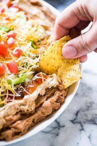 ¡Este saludable Taco Dip hecho con 5 capas de deliciosos ingredientes está listo en menos de 10 minutos y es el aperitivo perfecto para cualquier fiesta!
