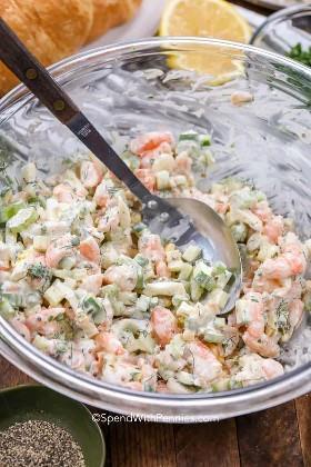 Un bol de ensalada de camarones con una cuchara de metal.