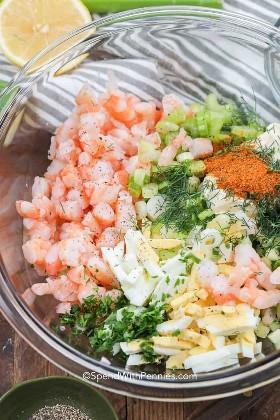 Un tazón para mezclar lleno de ingredientes de ensaladas de camarones, como camarones, huevos, apio y eneldo.