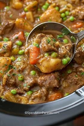 Un cucharón de cucharón de guiso de carne crockpot para servirlo.
