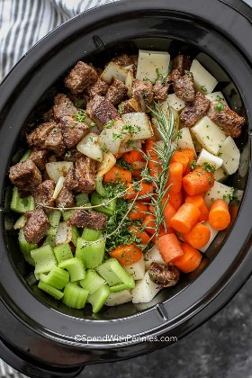 Ingredientes para el estofado de carne Crockpot en una olla de cocción lenta como papas, zanahorias, apio, ternera y romero.