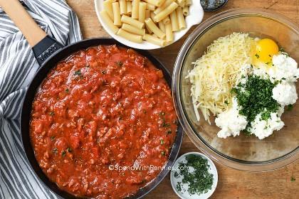 Ingredientes preparados para hacer ziti al horno con queso ricotta y salsa de carne.