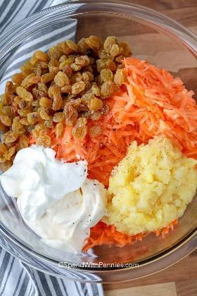 Ingredientes para ensalada de zanahoria incluyendo aderezo, pasas y piña
