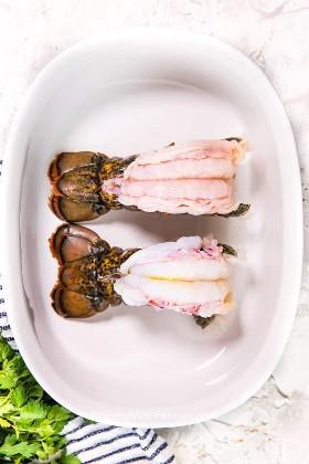 Dos colas de langosta con mantequilla en un plato para hornear blanco listo para el horno