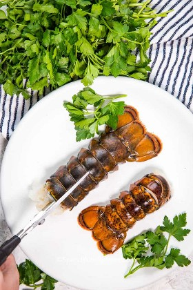 Las tijeras de cocina se utilizan para cortar la cola de langosta. Dos colas de langosta en un plato blanco con aderezo de perejil