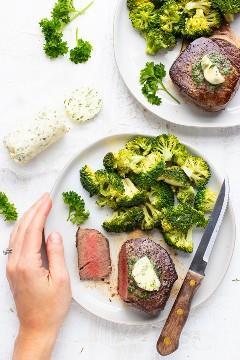 Una mano que sostiene un plato con una receta de filet mignon, brócoli y un cuchillo al lado de un tronco de mantequilla de hierbas de ajo.