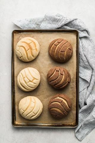 Conchas de chocolate y vainilla en una bandeja para hornear forrada con papel pergamino.