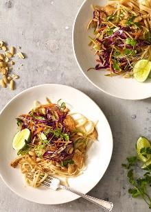 Fideos asiáticos de cacahuate con pollo, Lightened Up es delicioso, hecho con tiras de pollo salteadas, tallarines de arroz, cebolletas, zanahorias, ensalada de brócoli, brotes de soja en una salsa picante de maní. Una combinación ganadora de picante, crujiente, dulce y salada cautivará sus papilas gustativas.