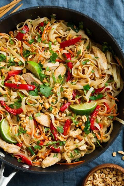 Pad Thai en un wok negro con pollo y verduras frescas.