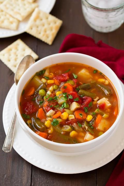 Una sola ración de sopa de verduras saludable en un tazón blanco sobre un plato blanco. Sobre una mesa de madera oscura con una servilleta roja a un lado.