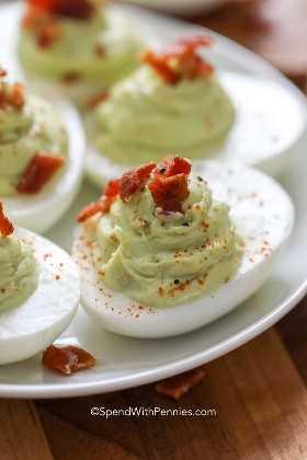 Huevos de aguacate con tocino en un plato listo para servir
