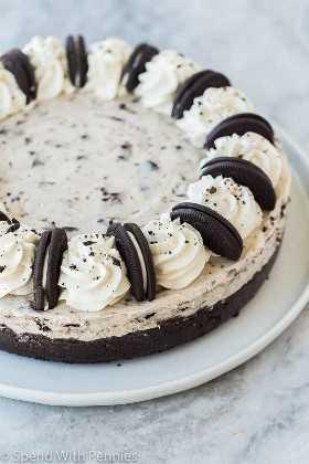 No hornee oreo cheesecake entero en un plato blanco adornado con Oreos enteros y crema batida