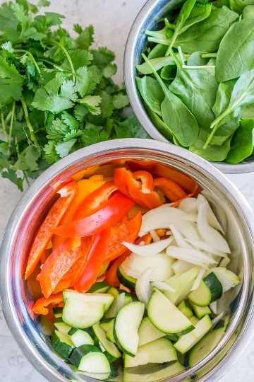 Rodajas de calabacín, pimientos, cebolla y espinacas baby para la receta de pasta de fajita de pollo