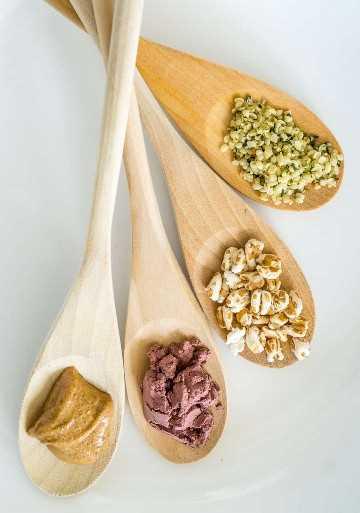 Imagen de ingredientes para el tazón de queso batido: semillas de cáñamo, trigo inflado, polvo de acai y mantequilla de almendras
