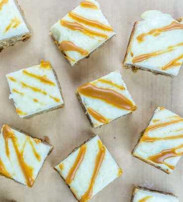 Disparo en la parte superior de trozos de canela Butterscotch Blondies rematado con queso crema y glaseado de caramelo | Babaganosh.org
