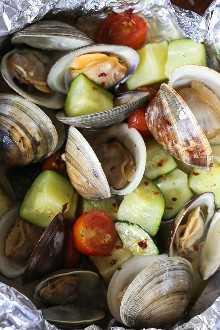 Pequeñas almejas a la plancha, cocinadas en paquetes de papel de aluminio con calabacín y tomates en una salsa de vino blanco con ajo, ¡tan rápida y fácil, perfecta para hacerla durante todo el verano!