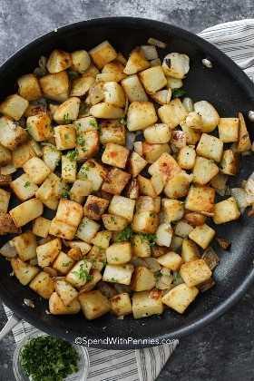 Una sartén de patatas fritas caseras salteadas con un poco de perejil fresco.