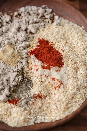 The spices for the homemade onion soup are mixed in a wooden bowl that includes onion flakes, broth, and paprika.