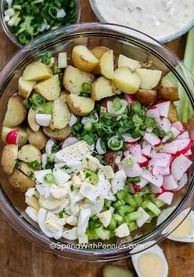 Ensalada de patata hecha en casa con los huevos que se preparan en un bol de vidrio.