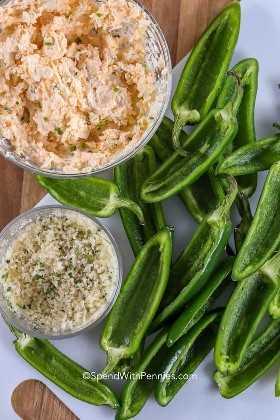 Jalapeños a la mitad, relleno de queso y pan rallado listo para ensamblar para hacer poppers jalapeños