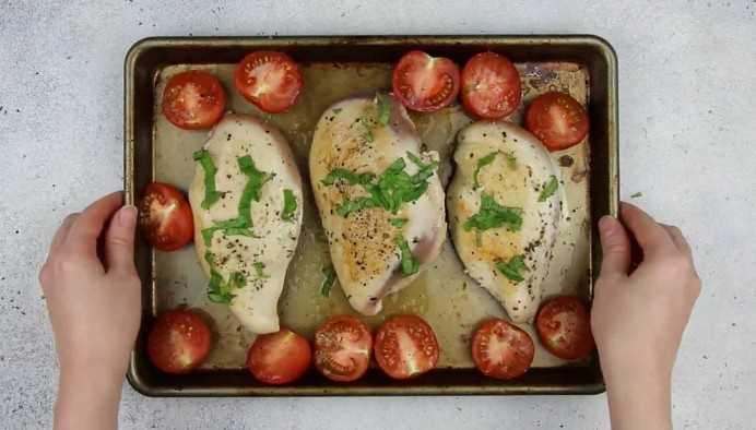 Imagen de pechuga de pollo rellena y tomates en una bandeja para hornear