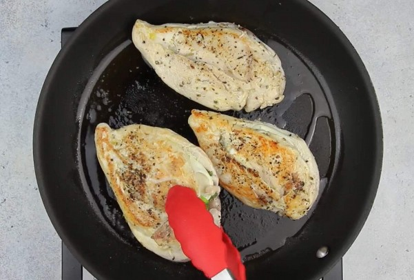 Imagen de pechuga de pollo rellena cocinando en sartén