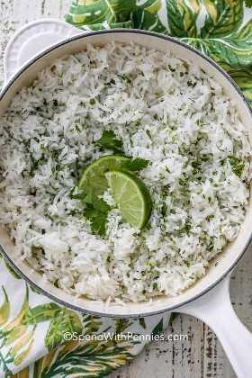Una olla de arroz de cilantro y limón listo para servir, cubierto con gajos de limón y cilantro.