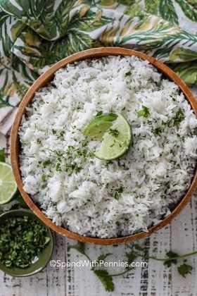 Un disparo en la parte superior de arroz con limón y cilantro con gajos de limón y un cuenco verde de cilantro picado.