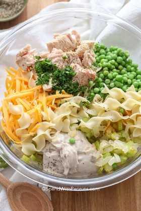 Ingredientes para una cazuela de atún fácil en un recipiente transparente que incluye atún, fideos de huevo, apio y guisantes.
