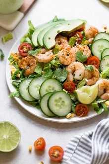 La Ensalada Cobb de Camarón Mexicano es una ensalada bellamente en capas con camarones, aguacates, maíz asado, salsa de frijoles negros, pepinos, tomates y queso.