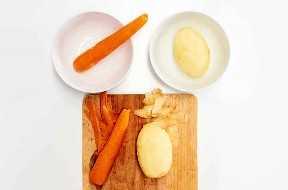 Zanahorias y patatas peladas en la tabla de cortar