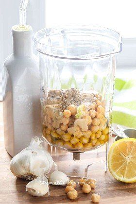 Ingredientes hummus en una licuadora como garbanzos, ajo, limón y especias.