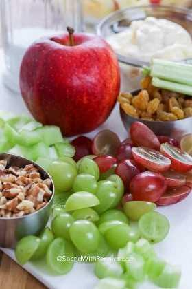 Ingredientes de la ensalada Waldorf: uvas, apio, manzanas y nueces en una tabla para cortar.