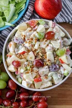 Ensalada Waldorf en un tazón para servir lleno de manzanas cremosas, zanahorias y otros ingredientes.