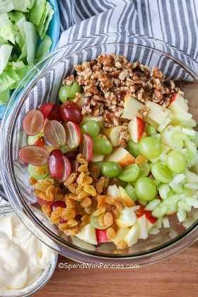 Un tazón claro lleno de ingredientes para ensalada Waldorf listo para ser arrojado.