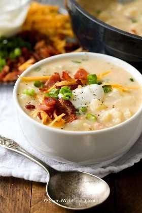 Un tazón de sopa de papa al horno cargada con una sopa en un tazón blanco