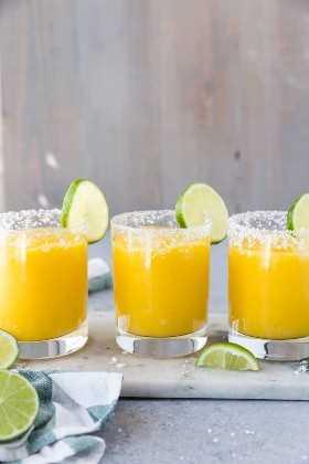 Tres vasos alineados en una tabla de mármol con bordes de sal y gajos de lima y rellenos de mango margarita congelada