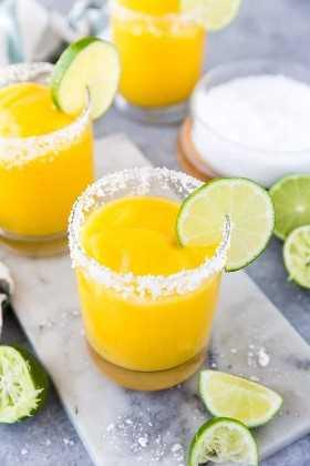 Un vistazo de arriba abajo a las margaritas de mango congeladas en vasos redondos con bordes de sal y cuña de limón con sal y limas al fondo