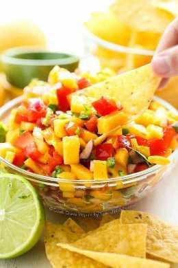 Salsa fresca de mango en un tazón claro con chips de tortilla y limón