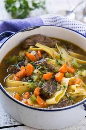 carne de res tierna estofada y sopa de fideos con huevo y fideos de huevo en una olla grande