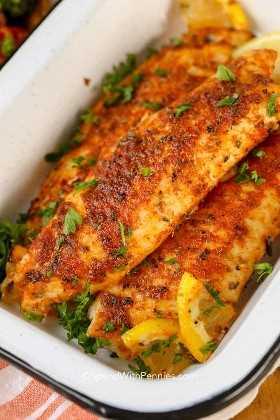 Tilapia ennegrecida en un plato de servir con limón para crear la mejor receta de pescado ennegrecido.