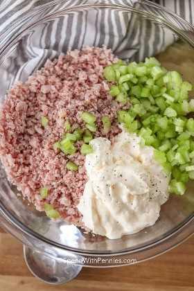Ingredientes de la ensalada de jamón en un tazón claro para mezclar piojos, jamón, apio y mayonesa.