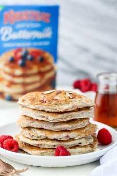 Una gran pila de panqueques de frambuesa con una caja de Kusteaz Buttermilk Pancakes se mezclan en el fondo