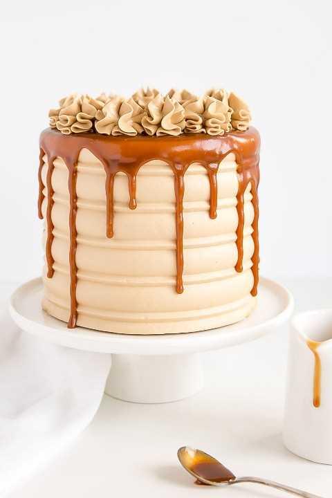 Pastel de caramelo con una pequeña jarra de caramelo al lado. Caramelo por goteo y rosetones.