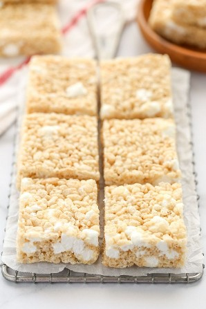 Varias rodajas de krispie de arroz se trata sobre un papel de pergamino.