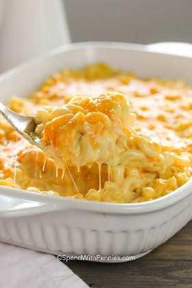 Una cuchara de servir de macarrones y queso pegajosos con sobre la mesa