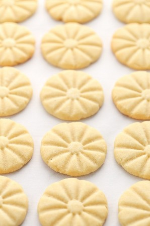 Una bandeja para hornear cubierta de papel pergamino cubierta con galletas de mantequilla recién sacada del horno.