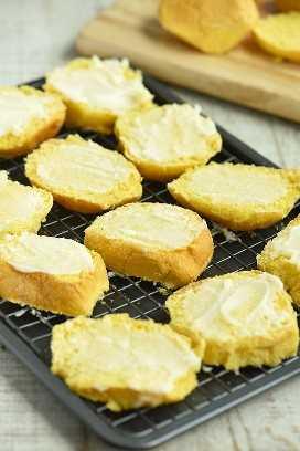 Rebanadas de pandesal con mantequilla y azúcar esparcidas sobre una rejilla para hornear para hornear biscocho