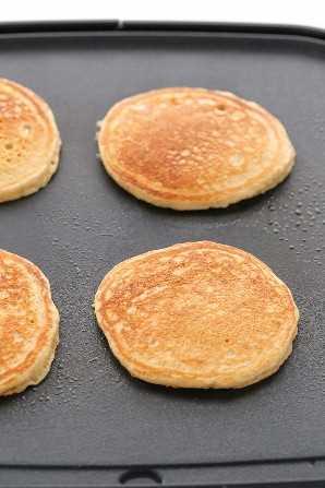 Una plancha negra cubierta con cuatro tortitas de trigo integral totalmente cocidas.